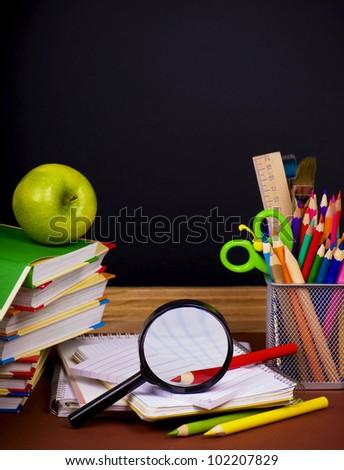 board,  books, pencils, opened empty notebook lie on school desk