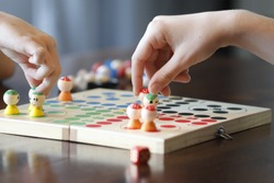 Board concentration game with children hand and colorful red and green figures