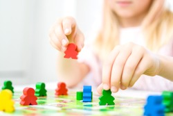 Board game and kids leisure concept - little blonde girl hold red people figure in hand. yellow, blue, green wood chips in children play