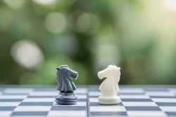Board game, business and planning concept. Close up of black and white chess knight pieces on chessboard with green nature background.