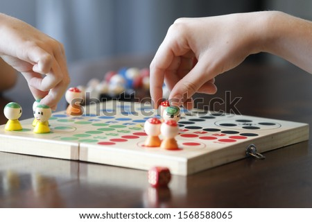 Board game with children hand, colorful figures and red die.