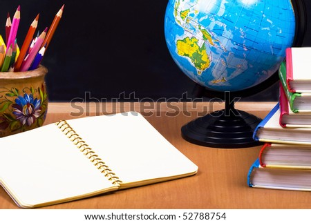 board, globe, books,  pencils, opened empty notebook lie on school desk