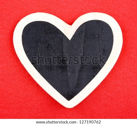 Board in heart shape on red background for message closeup