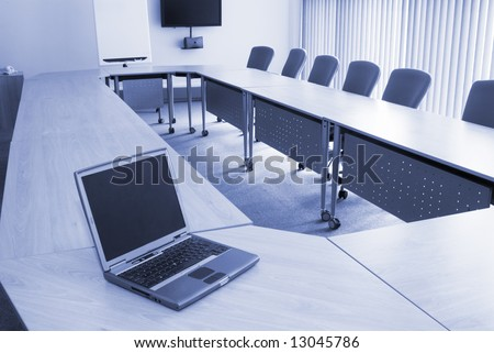 Board room in office block with laptop
