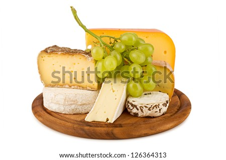 board with cheeses and white wine grapes.