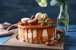 Board with delicious caramel cake on table