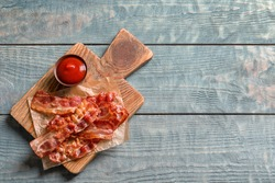 Board with fried bacon and sauce on wooden background