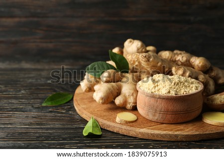 Board with ginger and ginger powder on wooden background Photo stock ©