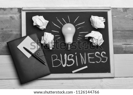 Board with light bulb, yellow chalk, pen and stickers. Process of creation: lamp, crumpled paper, chalk and notebook. White lamp as symbol of successful business idea. Business idea concept. #1126144766