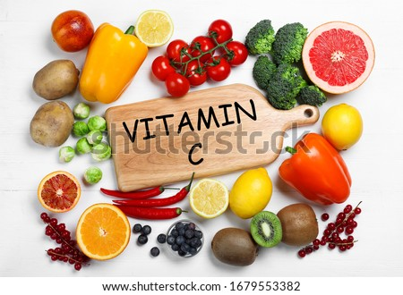 Board with phrase VITAMIN C and fresh products on white wooden table, flat lay
