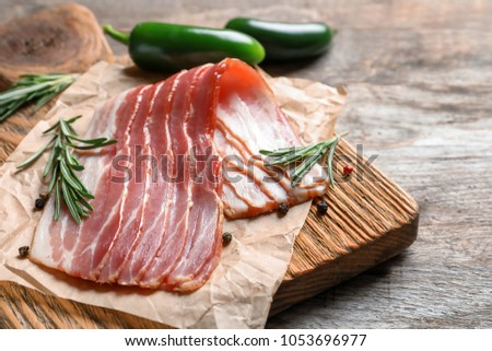 Board with raw bacon on table, closeup