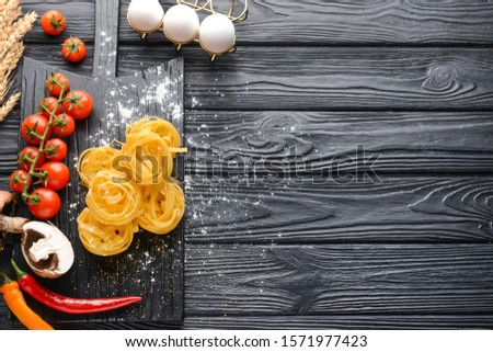 Board with uncooked pasta, mushrooms and vegetables on dark table