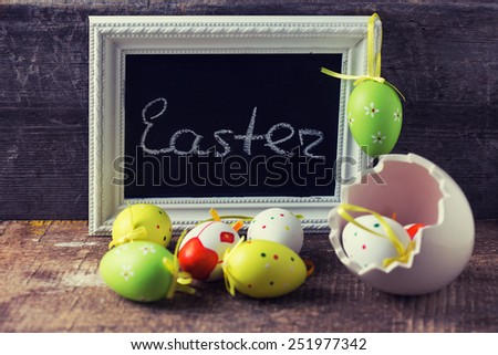 Board with word Easter and colorful easter eggs in pot on wooden background. Easter background. Selective focus. Toned image.