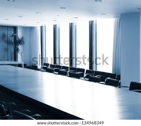 Boardroom conference room table brightly lit in blue colors