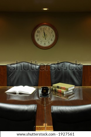 Boardroom lunchtime - empty seats, with open books and noontime clock prominent on wall in background. Photograph in one point perspective