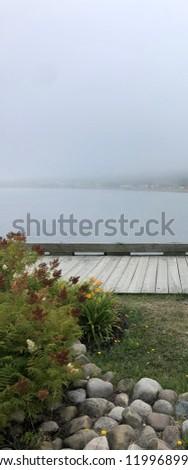 Boardwalk along riverbank on misty, hazy, overcast summer afternoon.