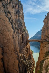 Boardwalk and footbridge of 'Caminito del Rey' mountain walk and hiking route.  Bridge between two steep mountains over the canyon and lake in the background. Path along steep cliffs. Andalusia, Spain