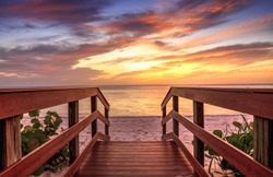Boardwalk leading to a Sunset over North Gulf Shore Beach along the coastline of Naples, Florida