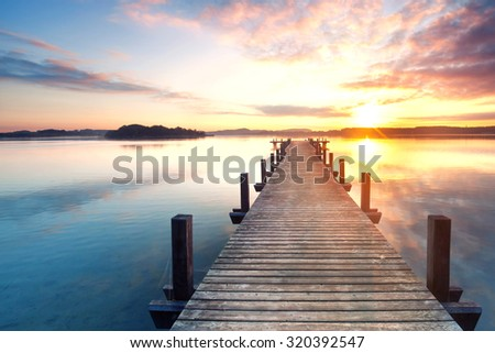 boardwalk leads out onto the lake, silent at lake while sunrise #320392547