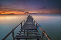 Boardwalk on beach at sunrise . Teluk Tempoyak, Penang, Malaysia. Copy Space Area