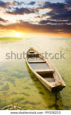 Boat at coast against a sunset. Nature composition.
