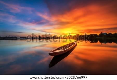 Boat at sunset on the lake. Sunset lake boat. Boat on sunset lake. Lake boat at sunset