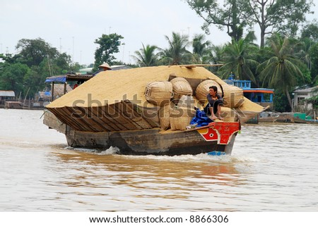 boat carrying rice on mekong delta, vietnam