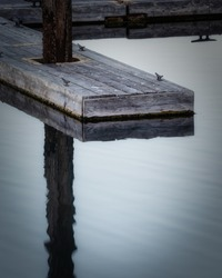 Boat dock reflection in calm water. High quality photo