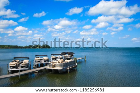 Boat dock with raised pontoons on beautiful lake in northern Minnesota with blue sky and fluffy clouds #1185256981