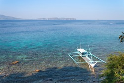 Boat for diving-trips docked over coral reef in Batangas, Philippine.