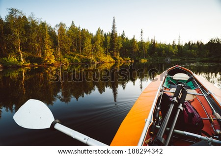 boat goes over the smooth water of the lake before sunset