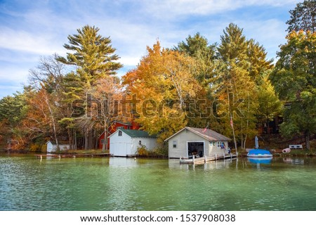 Boat houses on a lake during autumn, focus on boathouses #1537908038