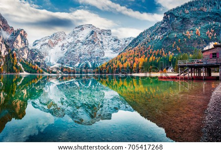 Boat hut on Braies Lake with Seekofel mount on background. Colorful autumn sunrise of Italian Alps, Naturpark Fanes-Sennes-Prags, Dolomite, Italy, Europe. Traveling concept background. - Shutterstock ID 705417268