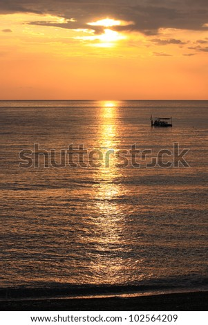 boat in a calm sea, not far from shore at sunset