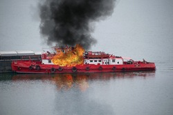 Boat in flames. Fire on board a ship pushing barges.