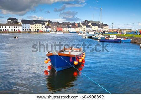 Boat in Galway Bay in front of old Galway Town and it's pastel buildings.