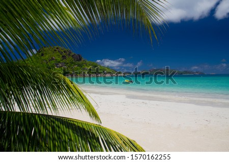 Boat in ocean with palm trees in Cote d'Or, Anse Volbert, Praslin Island, Seychelles