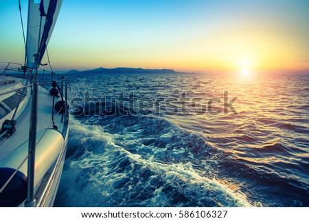 Boat in sailing regatta during sunset.