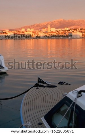 Boat in the port of Split, Croatia. Split promenade in the background, illuminated by pink sunset light. Selective focus.