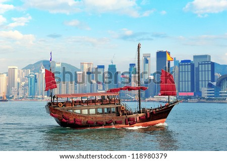 Boat in Victoria Harbor in Hong Kong with city skyline in the day