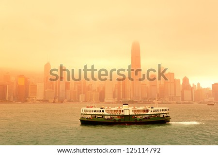 Boat in Victoria Harbor in Hong Kong with city skyline in the day in red tone