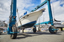 Boat-lift is lifting and transporting a boat in a boatyard for maintenance, repairs and cleaning in a sunny day