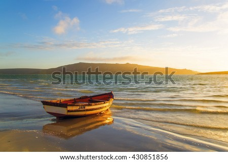 Boat moored at the Lagoon at sunset, West Coast, South Africa. This lagoon is a popular destination for fishermen, kite surfing and other water activities. The lagoon mouth in the Atlantic Ocean. #430851856