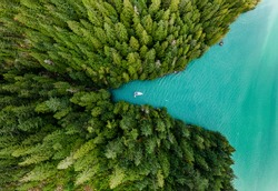 Boat moored in a cove with green forests all around aerial view