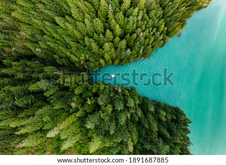 Boat moored in a cove with green forests all around aerial view Stock photo ©