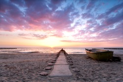 boat of a fisherman is located on the beach during sunset, burning sky in summer at Baltic sea