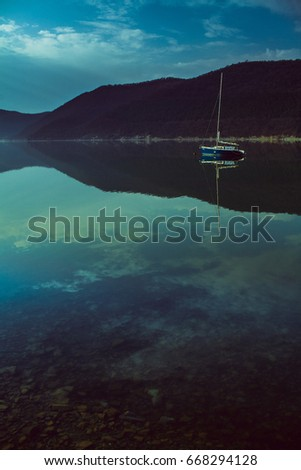 boat on a mirror calm lake with a lowered sail #668294128