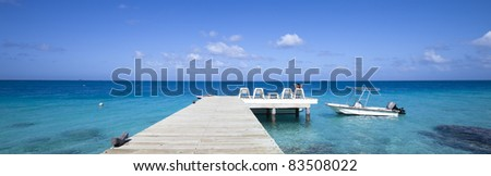 Boat on blue lagoon with a woman seat on chair of a pontoon in paradise island