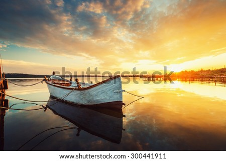 Boat on lake with a reflection in the water at sunset #300441911