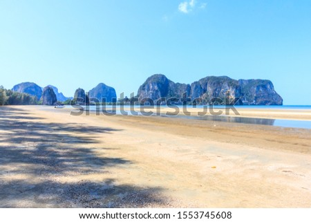 Boat on Rajamangala beach with limestone cliffs in the background,Trang province, Thailand